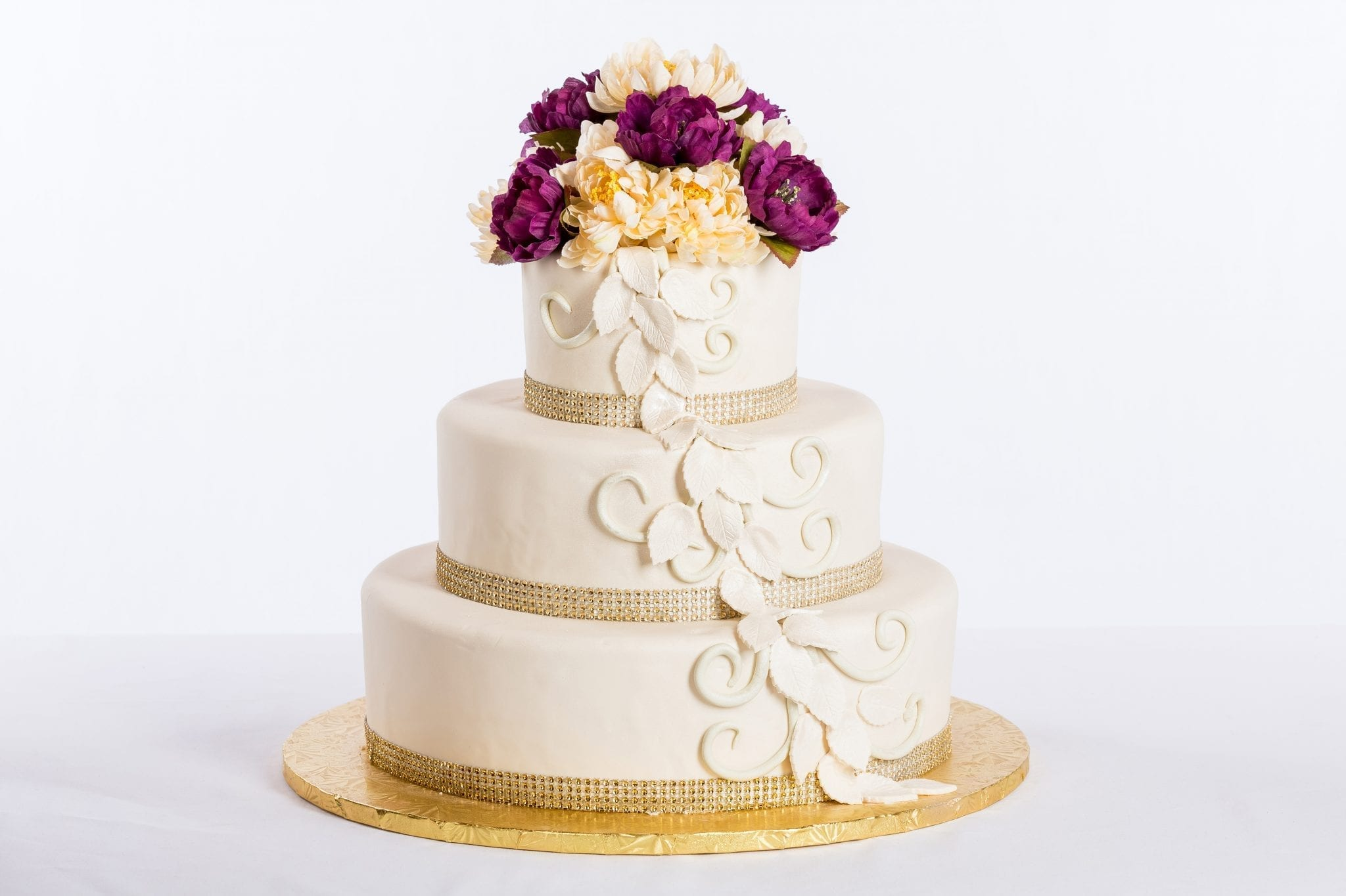 white wedding cake with gold ribbons and flowers on the side