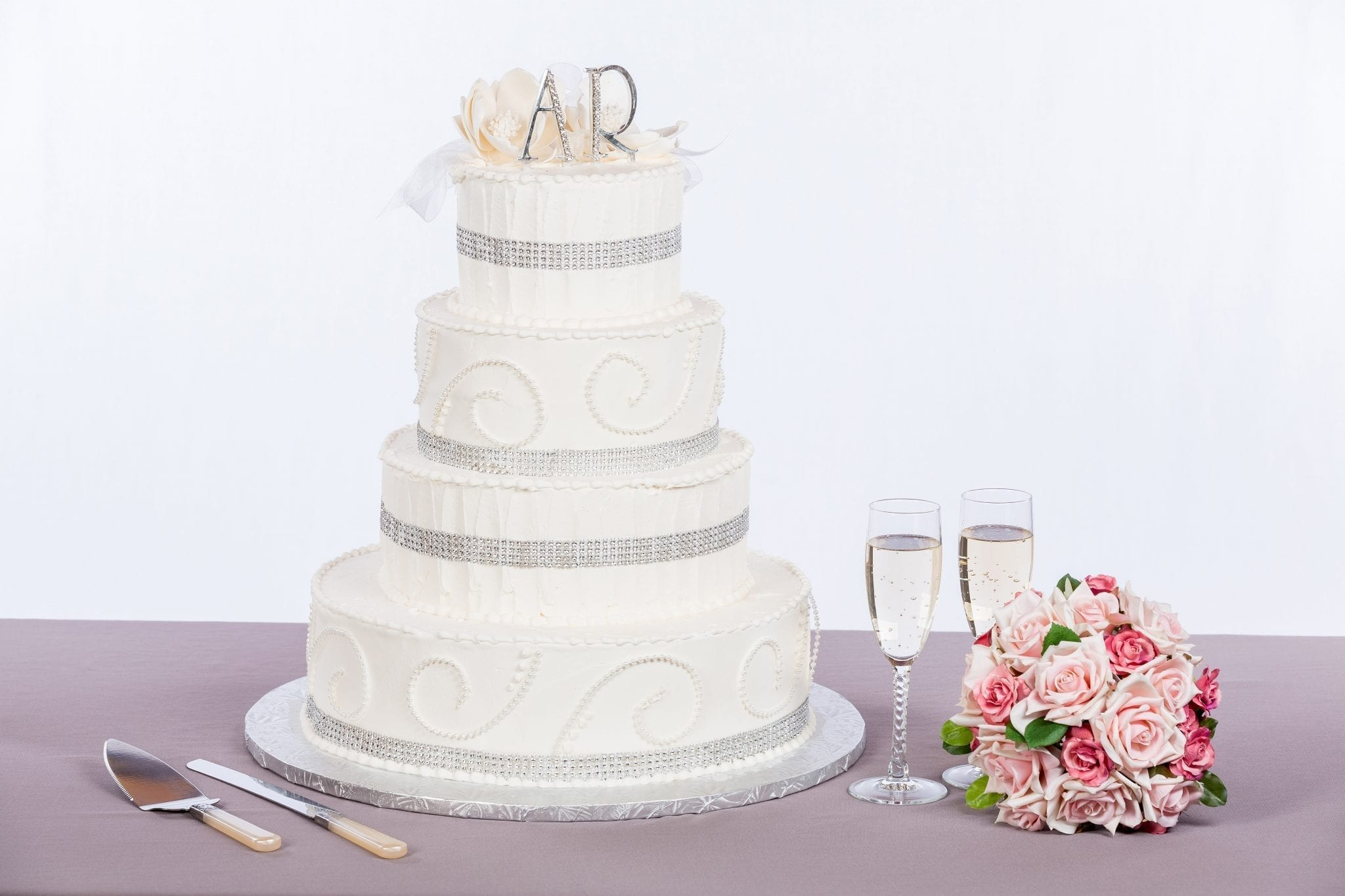 white wedding cake with silver ribbon