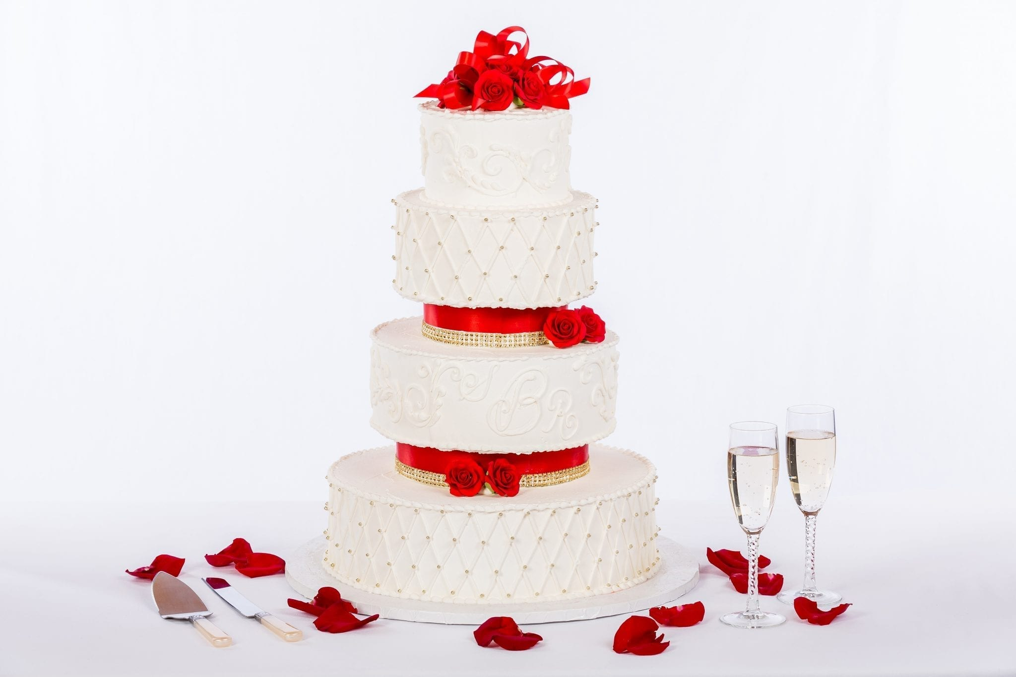 white wedding cake with red ribbons