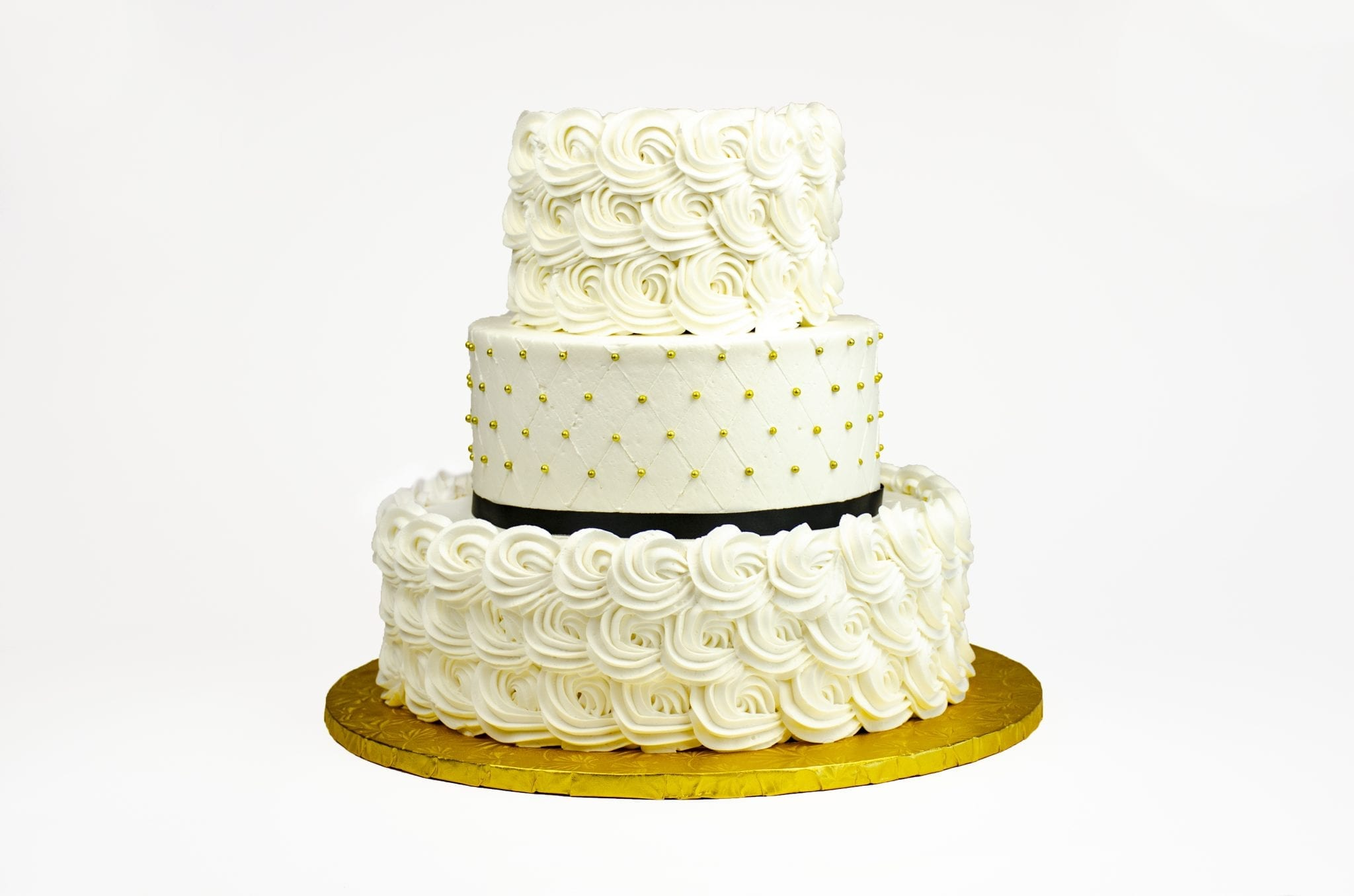 White and gold wedding cake with black ribbon